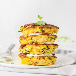 close up of stack of gluten-free butternut squash pancakes with yogurt sauce and fresh mint on top. White background