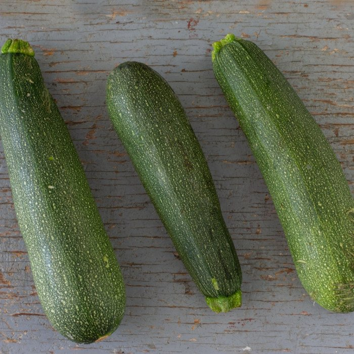 3 whole zucchini on weathered blue painted wood board