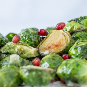 close up of roasted brussels sprouts with vanilla garlic butter toppes with pomegranate seeds