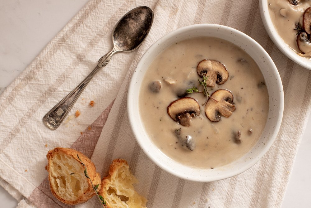 overhead view of white bowl with gluten-free creamy mushroom soup with spoon on left. Baguette slices. White and tan striped napkin in back ground