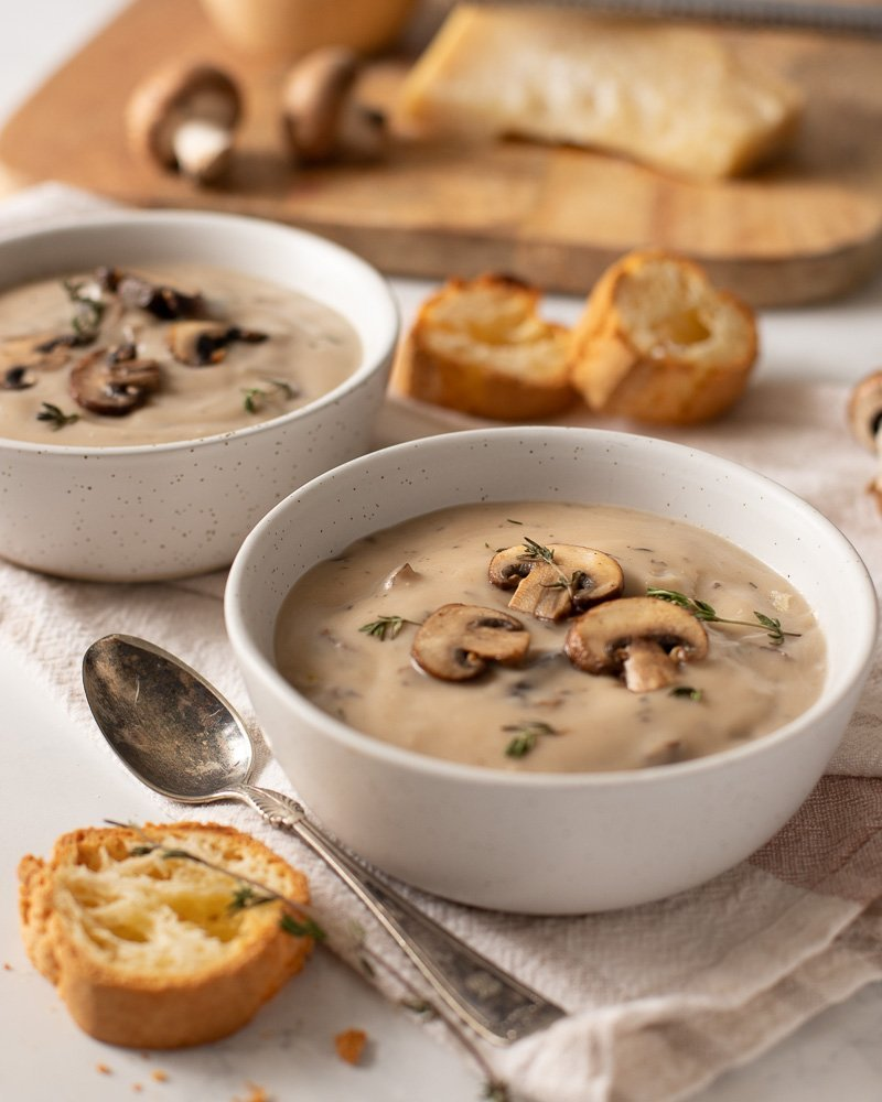 2 white bowls of creamy gluten free mushroom soup with sliced baguette and spoon on left. Mushrooms and block of parmesan cheese on board in background
