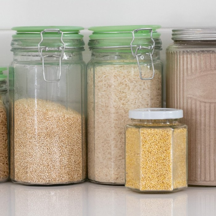 white kitchen counter with glass jars with gluten free grains and flours