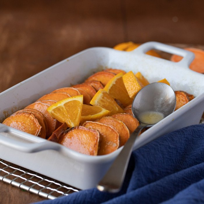 white baking dish with sliced roasted yams topped with orange slices. Blue napkin on right. Wood background.