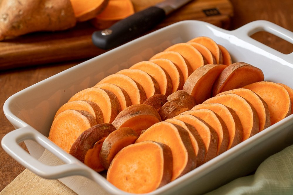 white baking dish with sliced yams. Cutting board with cut yam and knife in background.