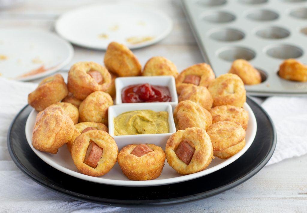 Gluten-free corn dog bites on round white plate with square bowls of mustard and ketchup in middle. Muffin tin in background