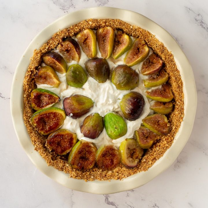 overhead view of gluten-free fig pie on white marble background