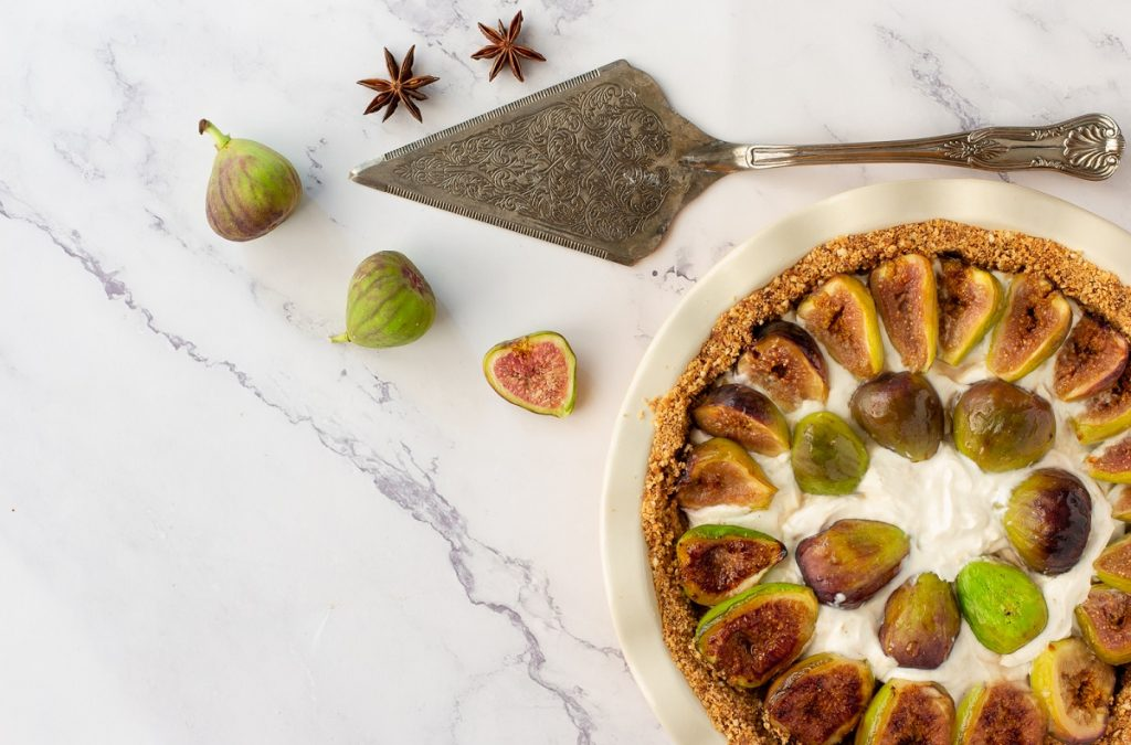 overhead view of gluten-free fig pie in corner of frame, with fresh figs, star anise and pie server