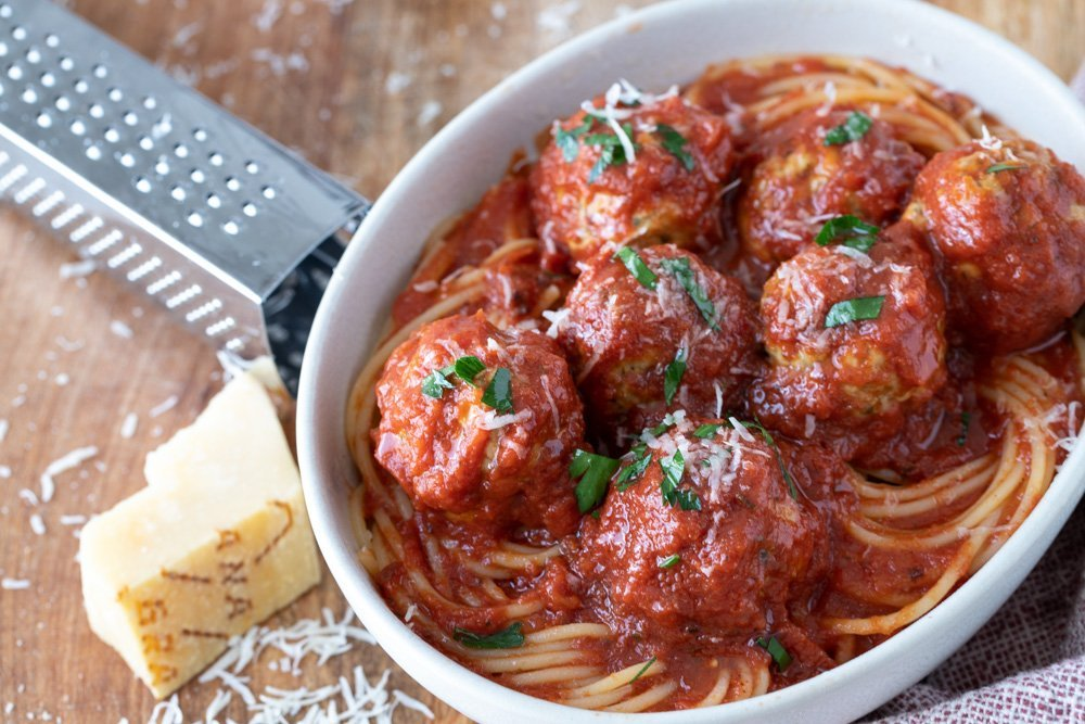 overhead view of white bowl with spaghetti and gluten-free meatballs with marinara sauce, Red and white napkin on right, cheese grater and wedge of parmesan on left. Wood background.