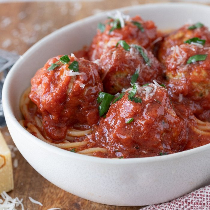 close up of white bowl with spaghetti and gluten-free meatballs with marinara sauce, Red and white napkin on right, cheese grater and wedge of parmesan on left. Wood background.