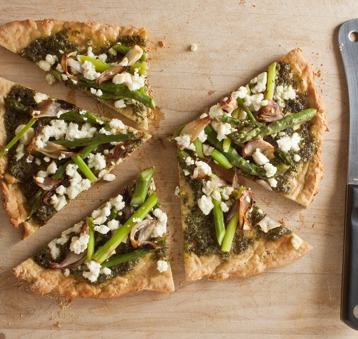 overhead shot of cut gluten free pizza with pesto, feta, shallot and asparagus on wood board with cleaver on right