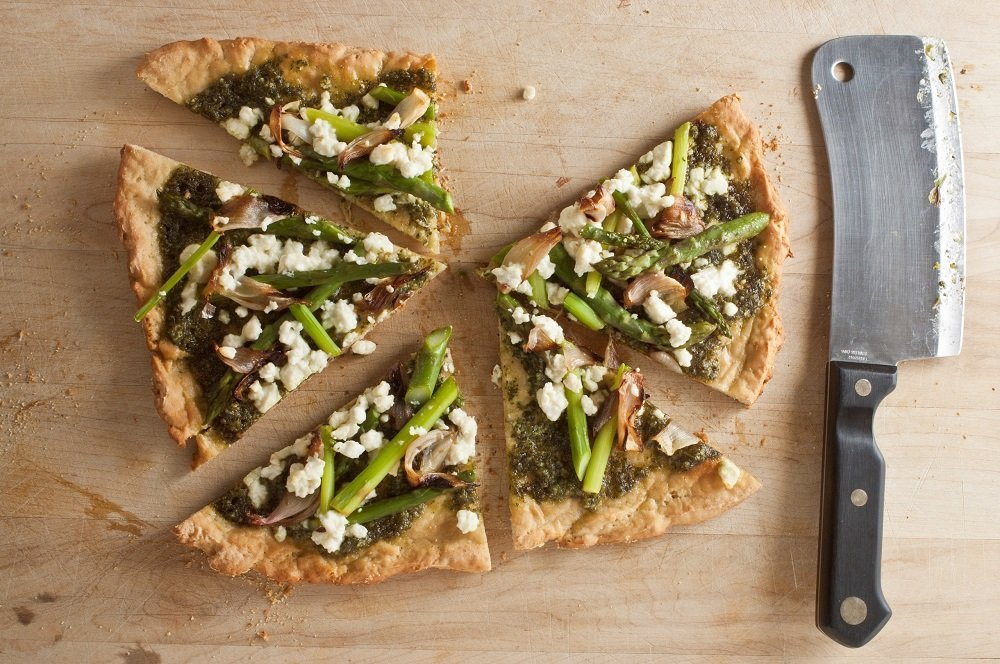 overhead shot of cut gluten-free pizza with pesto, feta, shallot and asparagus on wood board with cleaver on right