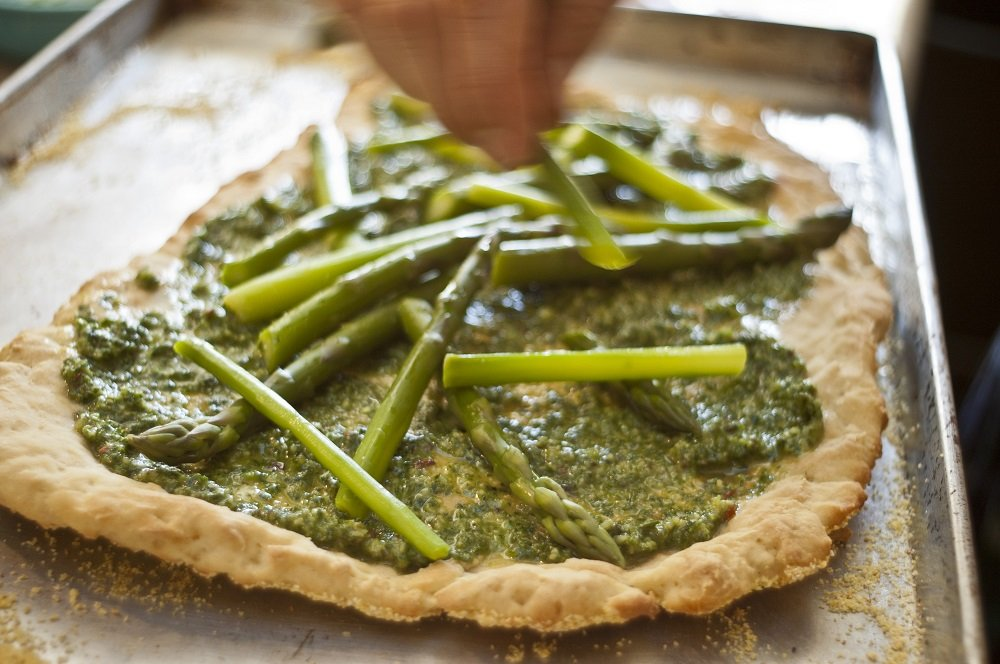 close up of gluten free pizza crust with pesto and asparagus spears on metal pan with hand above holding asparagus