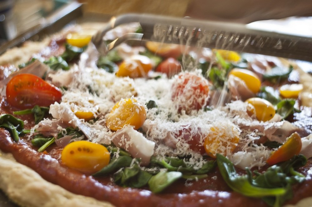 close up of gluten free pizza with yellow and red tomatoes, leafy greens, prosciutto with grater shredding cheese on top