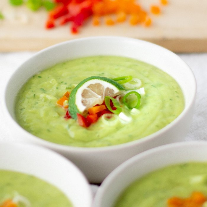 close up of white bowl with cool avocado soup garnished with red and orange bell pepper, green onion and lime slice