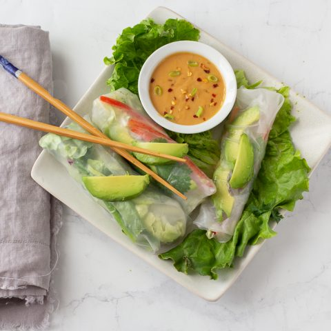 overhead view of gluten free spring rolls with white bowl of peanut sauce on bed of lettuce on square white plate. gray napkin and chop sticks on left