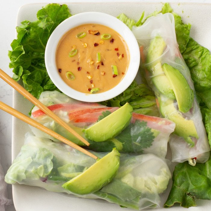 overhead view of spring rolls on bed of lettuce. White bowl with peanut dipping sauce, chop sticks on left