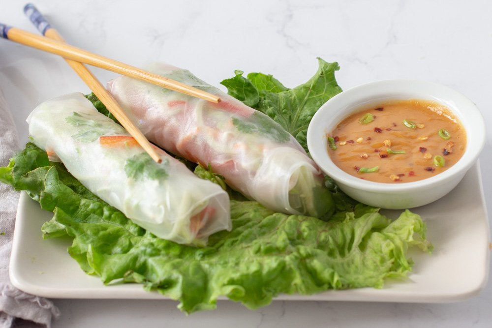 2 gluten free spring rolls on bed of lettuce on rectangular white plate with bowl of peanut sauce and chop sticks