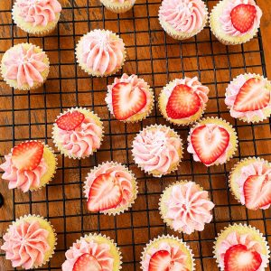 overhead shot of mini gluten-free cupcakes with strawberry frosting and strawberry slice on black wire rack