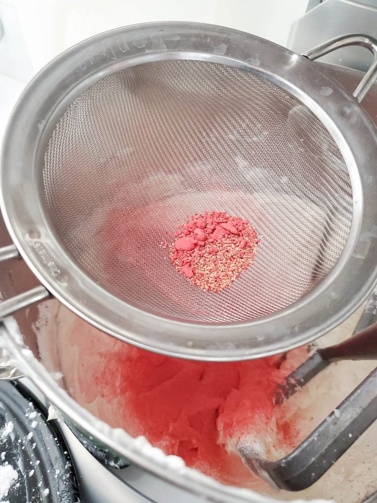 fine mesh strainer with dried strawberry powder sifting into bowl of white frosting