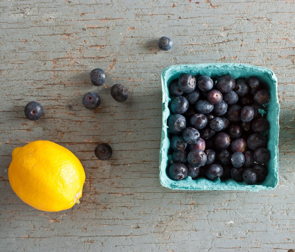 overhead shot of green pint container of blueberries with lemon on side on weathered blue background