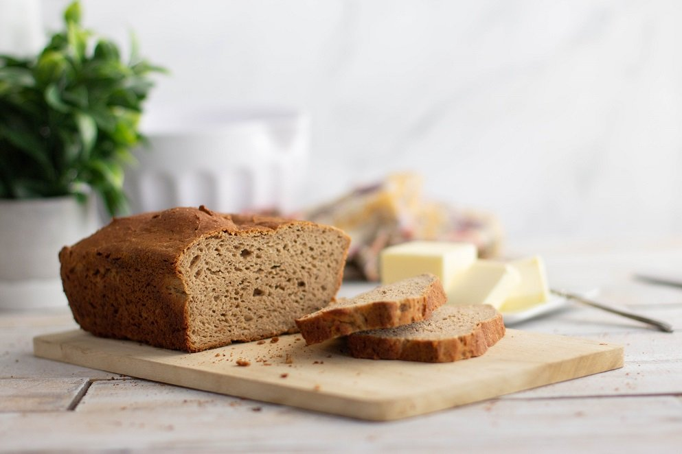 partially sliced loaf of gluten-free multi-grain bread on wood board with butter in plant in background.