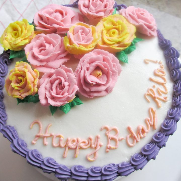 overhead view of layer cake with buttercream frosting and yellow and pink flowers