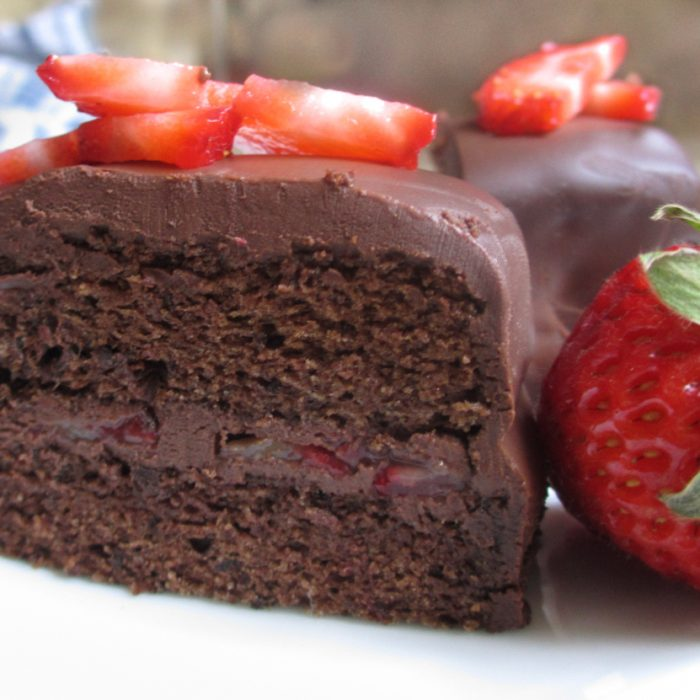 close up of square piece of 2 layer gluten free chocolate cake with chocolate ganache, sliced strawberries on top and whole strawberry to right.