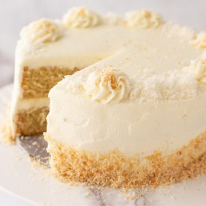 gluten-free coconut cake with white frosting, one wedge cut out, toasted coconut garnish, on white marble plate