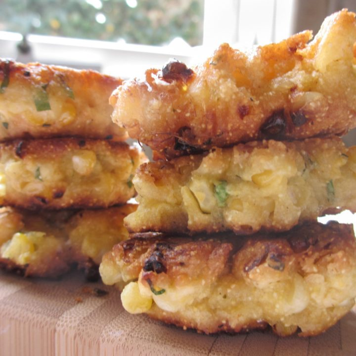 2 stacks of 3 corn fritters on wood board with window in background