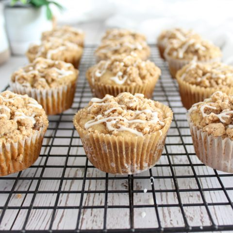 close up of 12 gluten free banana muffins with cinnamon crumble and white icing on black wire rack with weathered wood background