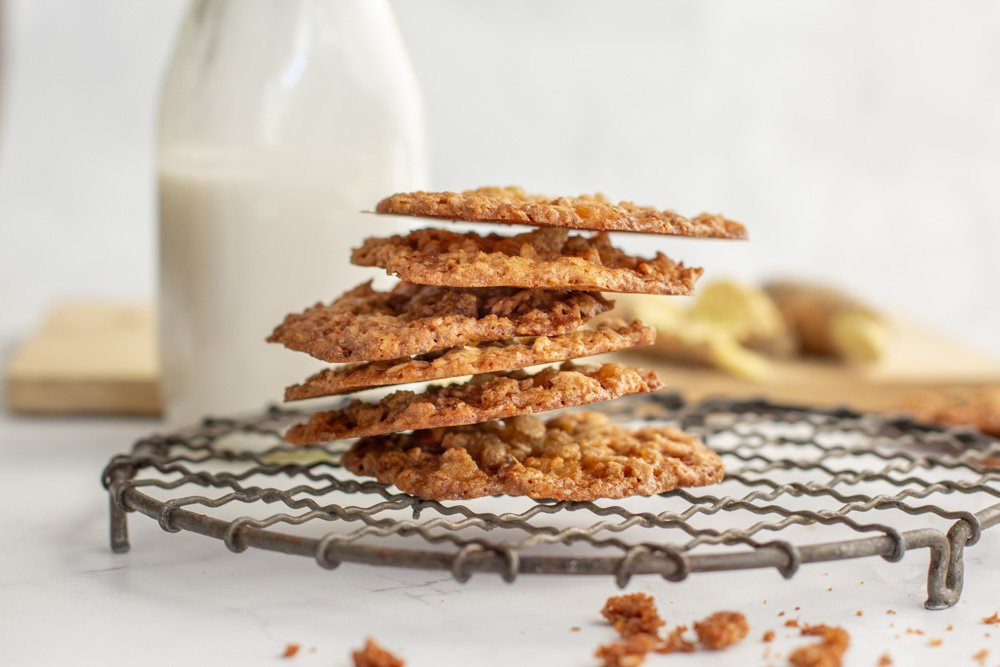 stack of ginger lace cookies on round wire rack with milk bottle and fresh ginger in background