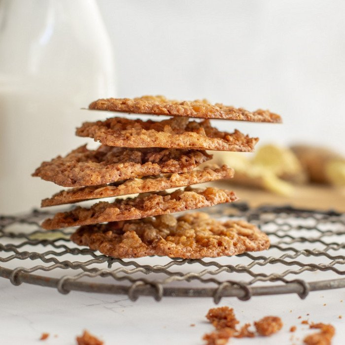 close up of stack of gluten free ginger lace cookies on round wire rack. Milk bottle and fresh ginger in background