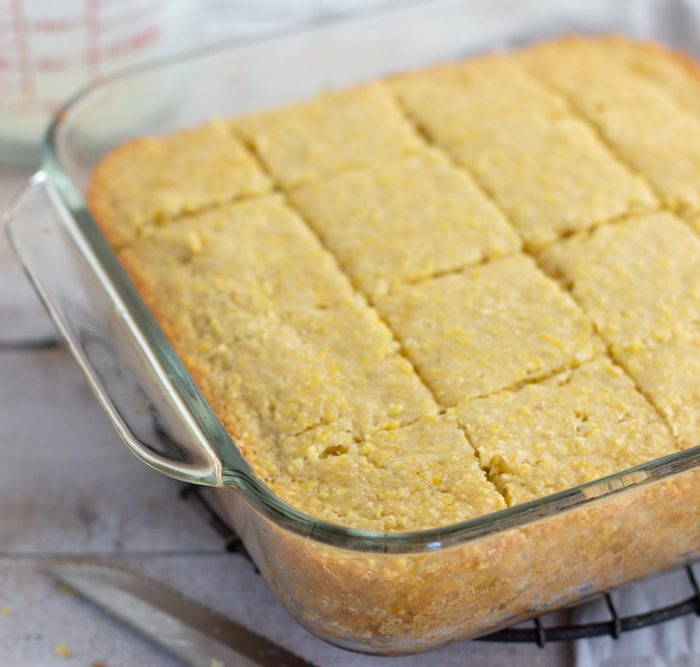 square glass pan of cut gluten-free cornbread with one piece on top, glass bowll of butter and honey bear on left and glass measuring cup in background