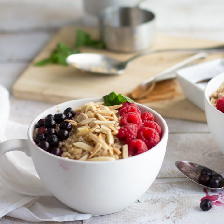 2 large white mugs with quinoa topped with blueberris, raspberries, slivered almonds and mint leaves with wood board with measuring cup, spoon and white bowl in background