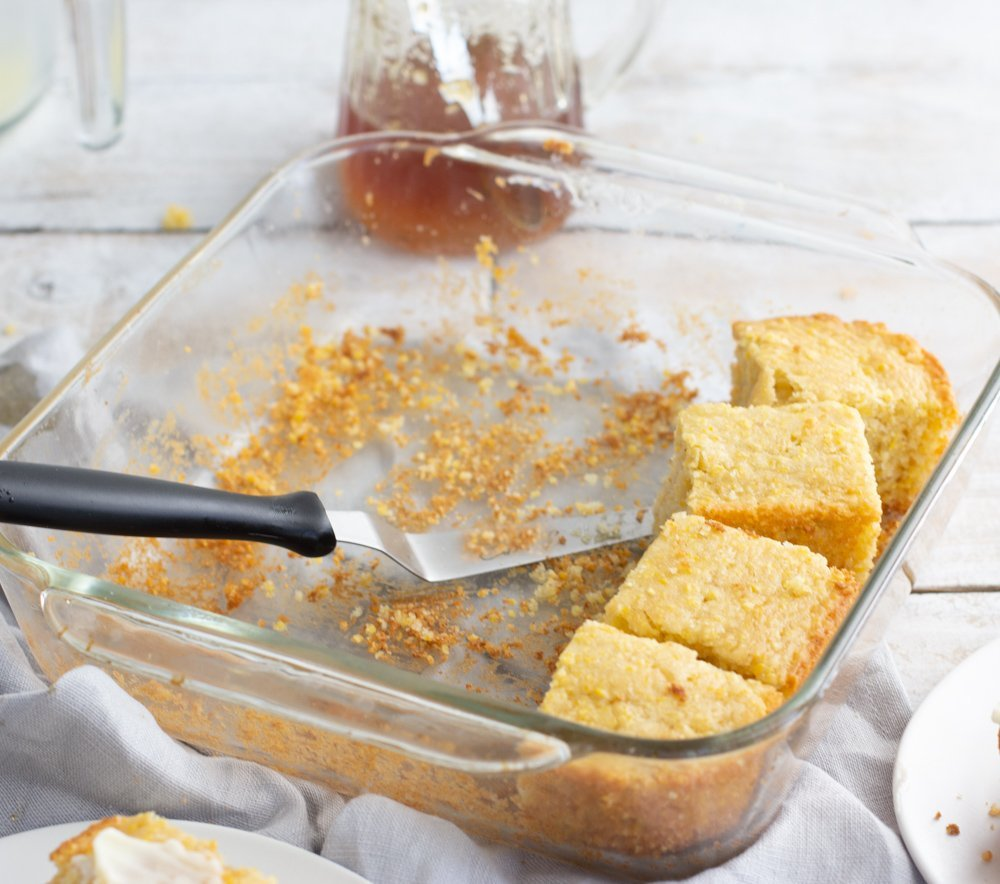 square glass baking dish with pieces of gluten-free corn bread, glass pitcher of honey in back