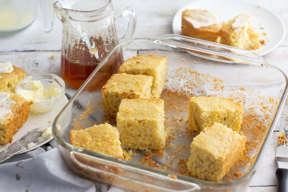 square glass baking dish with cut squares of gluten-free corn bread, glass pitcher of honey and plate of buttered squares of corn bread on white plate to left and in back
