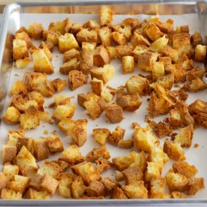 crispy baked gluten free croutons on metal baking sheet with parchment liner