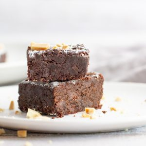 stack of 2 gluten free fuge brownies with powdered sugar and nuts on top on white plate