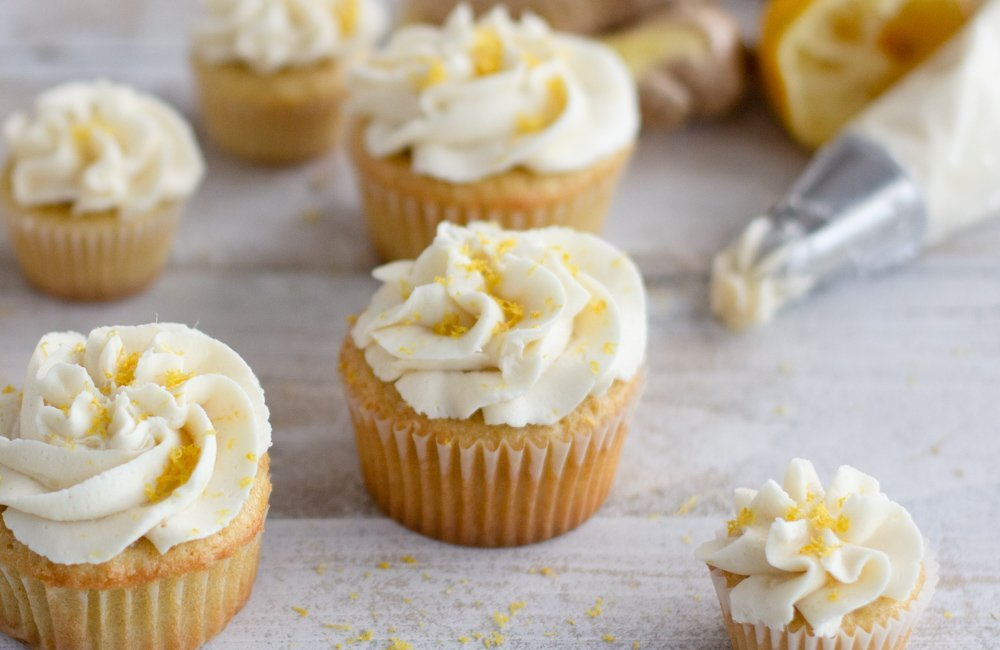 close up of gluten-free  ginger cupcakes with vanilla frosting on white wood background