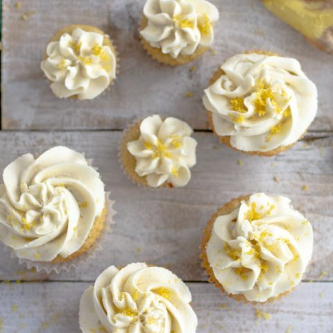 close up of gluten free ginger cupcakes with vanilla icing garnished with lemon zest on wood board
