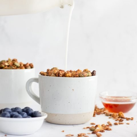 2 white mugs of granola with milk bottle above pouring into front bowl. small white bowl of blueberries infront. spilled granola and wood spoon on right, small glass bowl of honey in back on white background