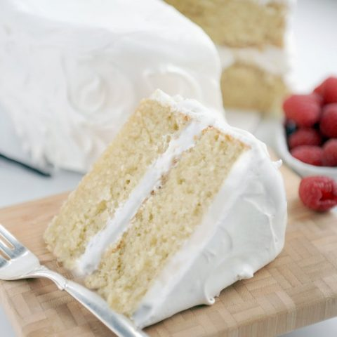 wedge of gluten-free vanilla cake with white frosting on wood board, raspberries and whole cake in background