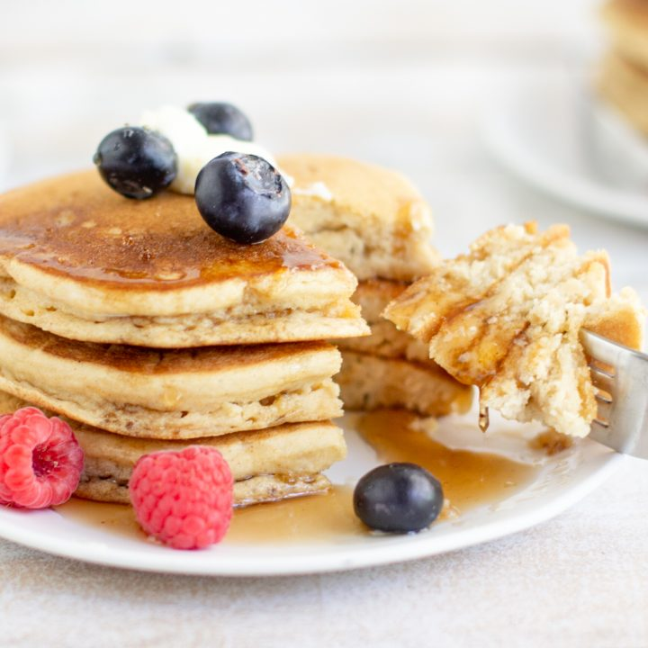 stack of gluten free pancakes, topped with blueberries and butter, wedge cut out on fork dripping with syrup