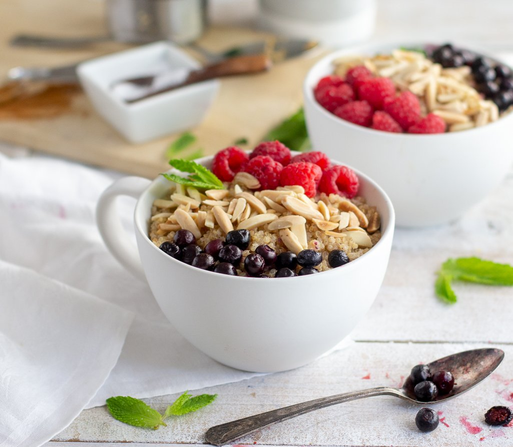 2 large white mugs with quinoa topped with blueberris, raspberries, slivered almonds and mint leaves with wood board with measuring cup and white bowl in background
