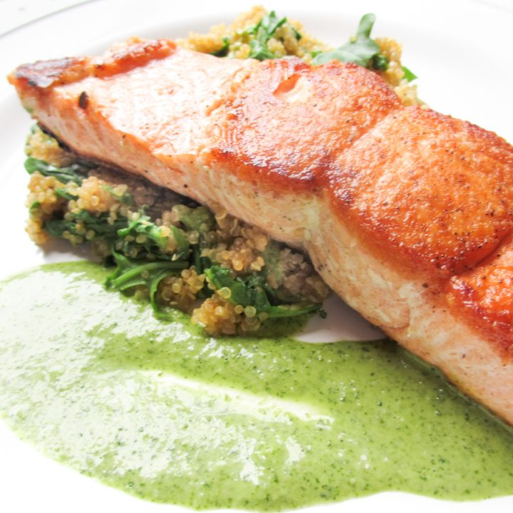 Salmon filet on white plate with cilantro lemon pesto