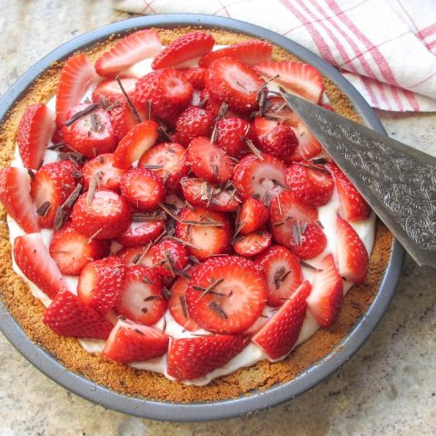 overhead of whole strawberry pie with silver pie server on stone background
