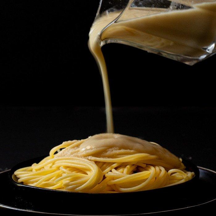 glass pitch pouring vegan cream pasta sauce onto gluten free pasta on black plate. Black background.