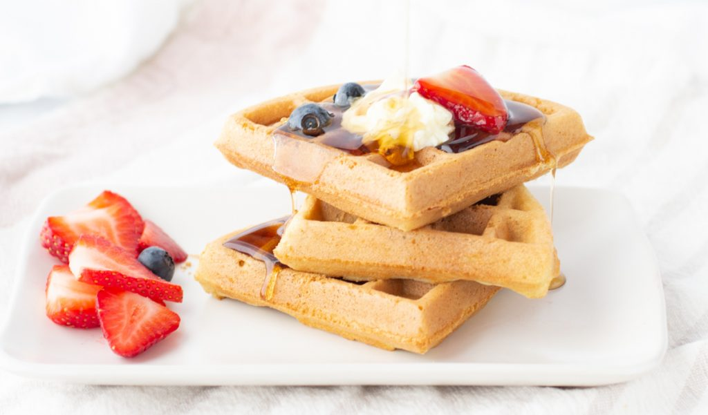 stack of 3 gluten-free waffles topped with strawberries, blueberries and butter with syrup pouring over.