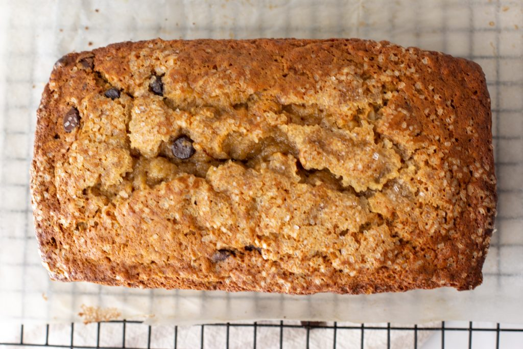 overhead shot of whole loaf of gluten-free dairy-free banana bread with chocolate chips on parchment paper and black wire rack