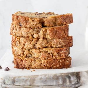 close up stack of gluten-free banana bread slices on white background with milk bottle in background